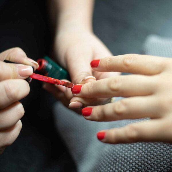 Pose de vernis rouge sur les mains